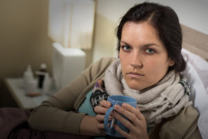 Portrait of woman having flu sore throat drinking tea